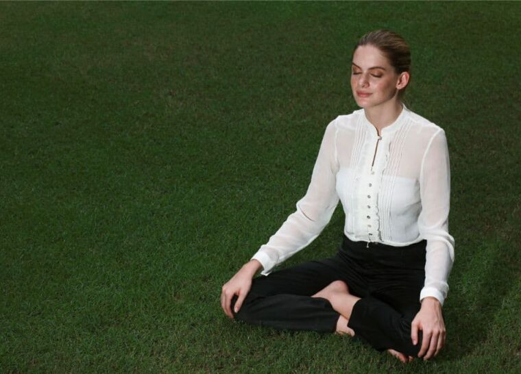 Businesswoman meditating on a field