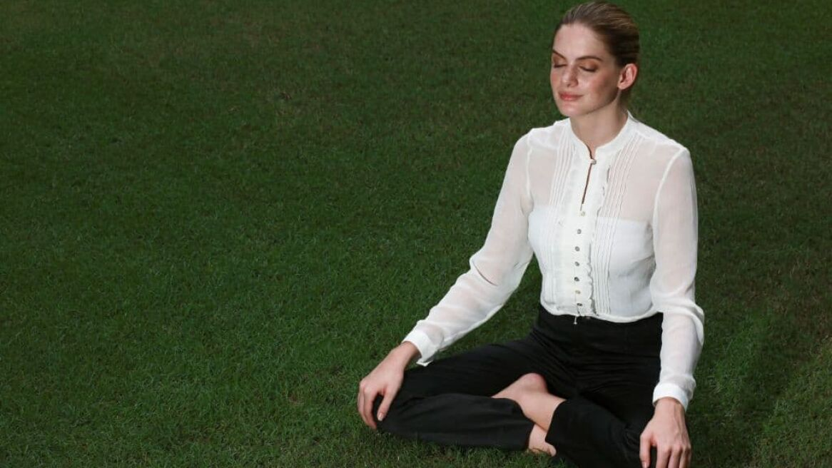 Businesswoman meditating on a field