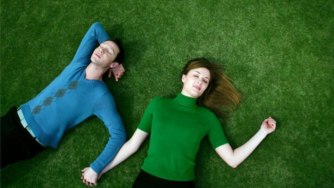 Couple Holding Hands Lying on Field
