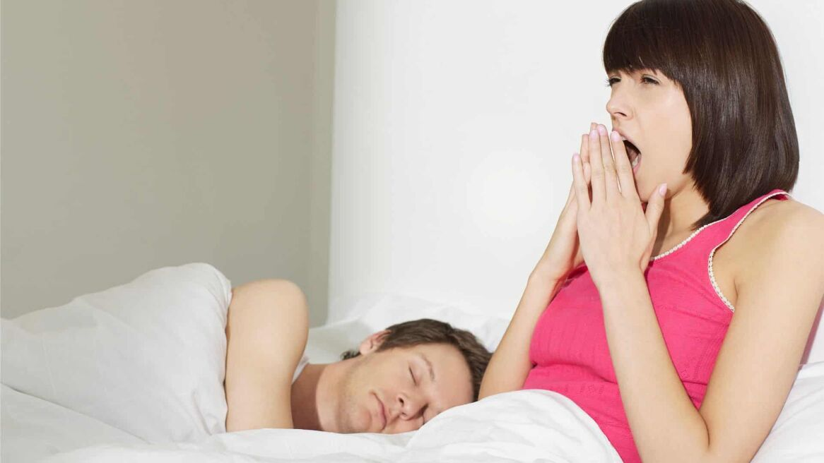 Young couple in bed man sleeping woman yawning