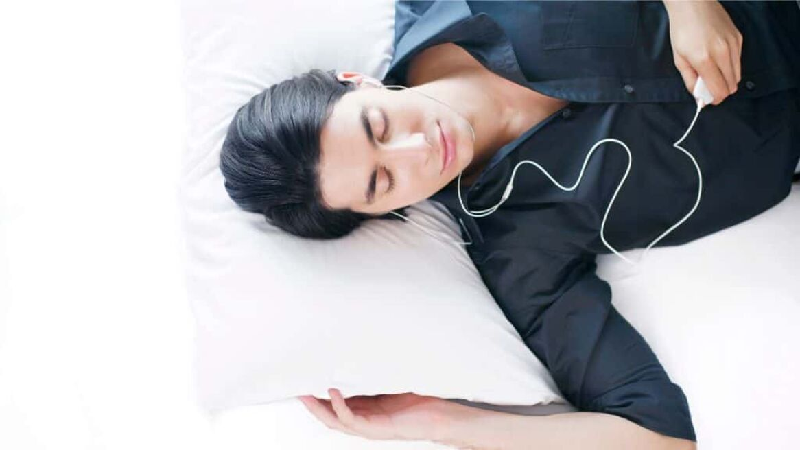 Man listeing to MP3 Player lying on bed
