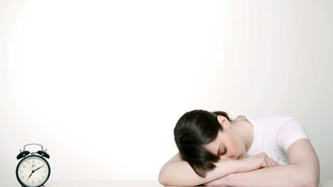 Woman Napping Beside Alarm Clock